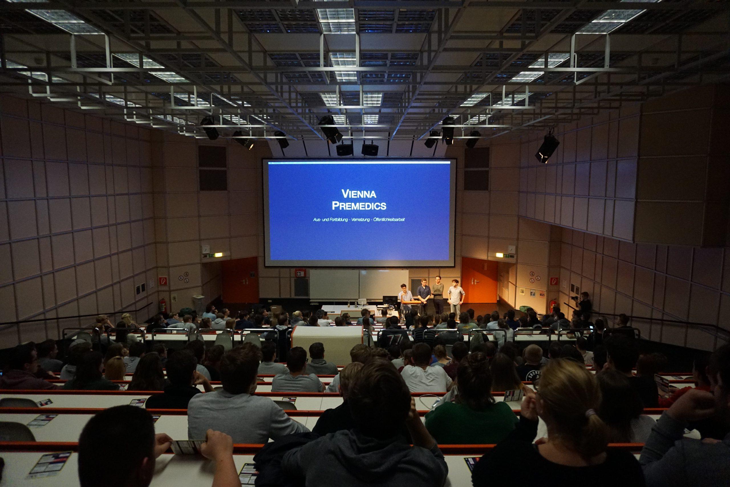 Foto des gefüllten Hörsaals mit Logo der Vienna Premedics
