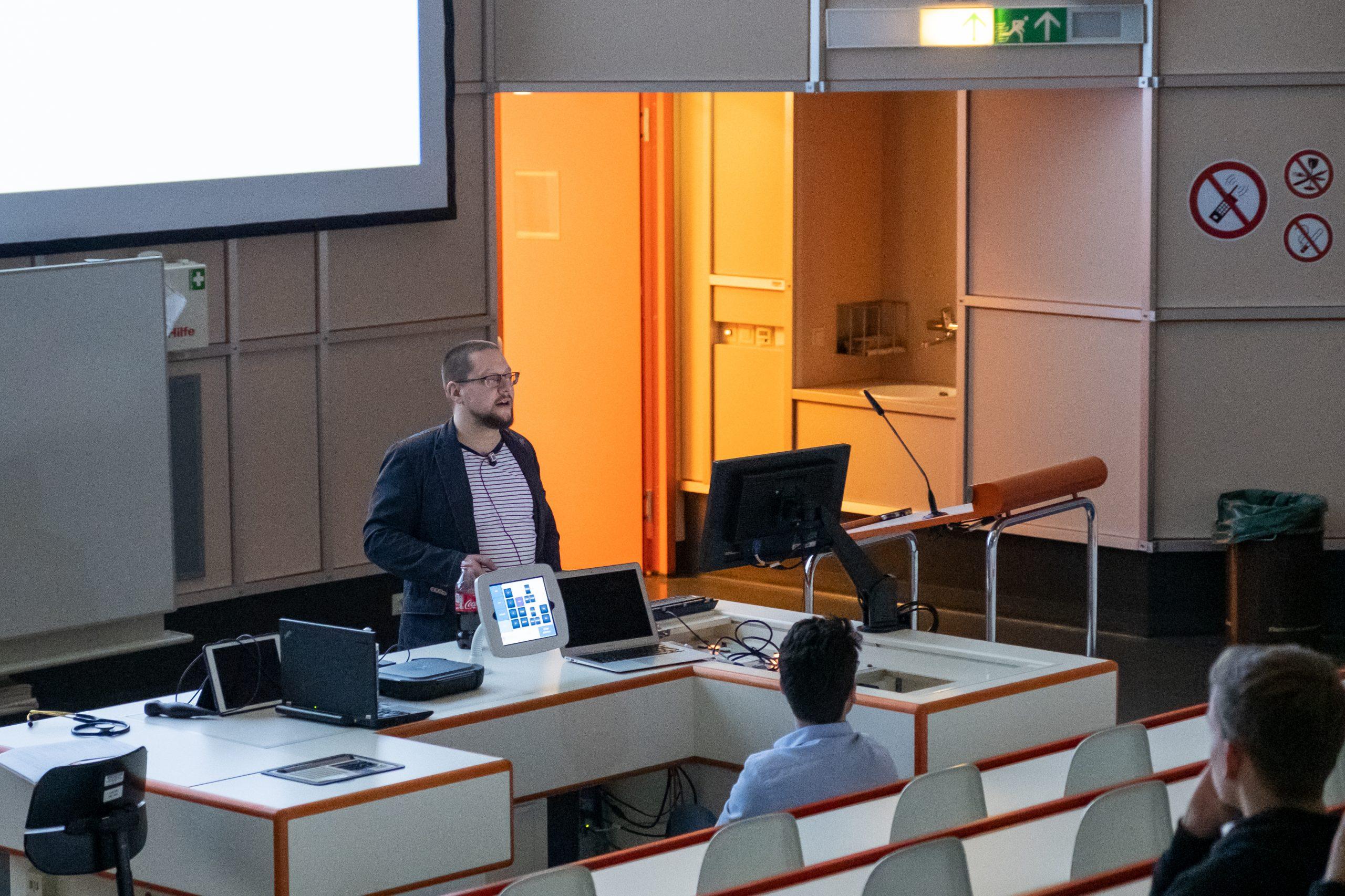 Vortragssaal mit dem Vortragenden, der ins Publikum spricht